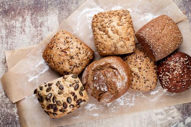 Золотые деревенские хрустящие буханки хлеба и булочки на деревянных фоне. натюрморт запечатлен сверху, плоская планировка.