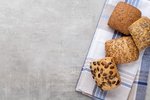 Золотые деревенские хрустящие буханки хлеба и булочки на деревянном фоне