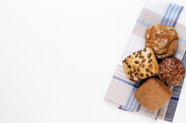 Золотые деревенские хрустящие буханки хлеба и булочки на деревянном столе. натюрморт запечатлен сверху, плоская планировка.
