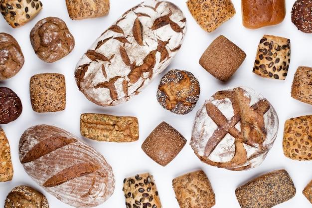 Золотые деревенские хрустящие буханки хлеба и булочки на деревянном.