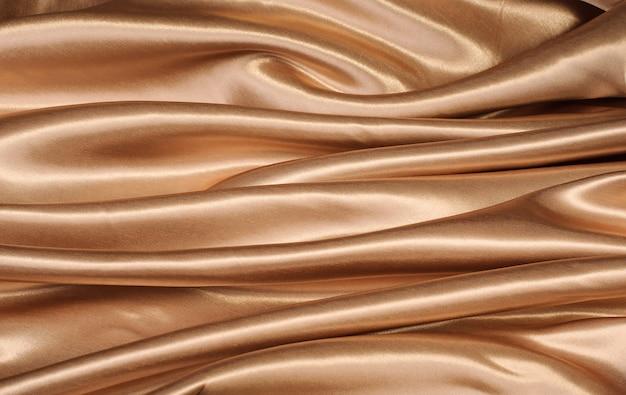Предпосылка ткани яркого блеска сатинировки золота с космосом экземпляра, предпосылками; текстурированный; текстиль; шелк