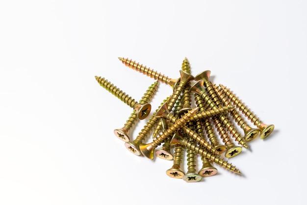 금색 나사는 흰색 표면에 무작위로 흩어져 있습니다. 노란색 아연 머리 나사