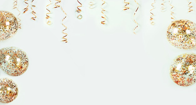 Gold serpentine holiday decoration and balloons with colorful confetti on light background