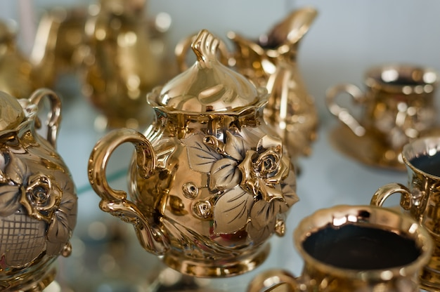 Gold set for coffee and tea with dimensional roses on the cups