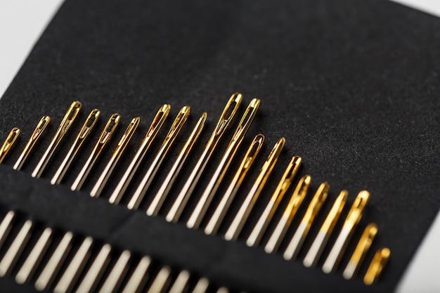 行の黒の背景にゴールドのミシン針。