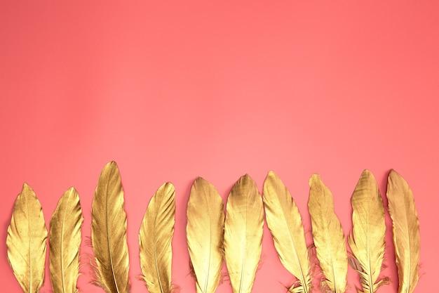 パステルピンクの背景にゴールドの光沢のある羽、フラットレイ、レトロ、モダン、カラフルなスタイリッシュなコンセプトの上面図。
