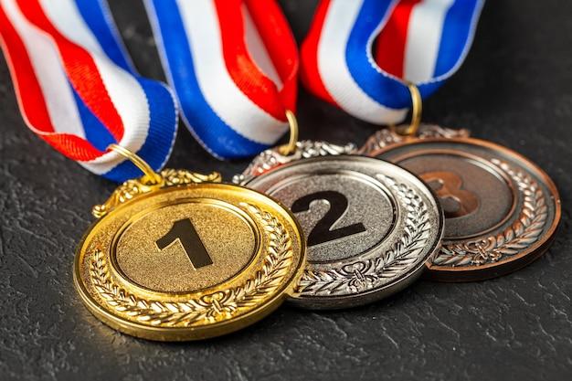 Золотая, серебряная и бронзовая медали с лентами. награда за первое, второе и третье место в соревновании.