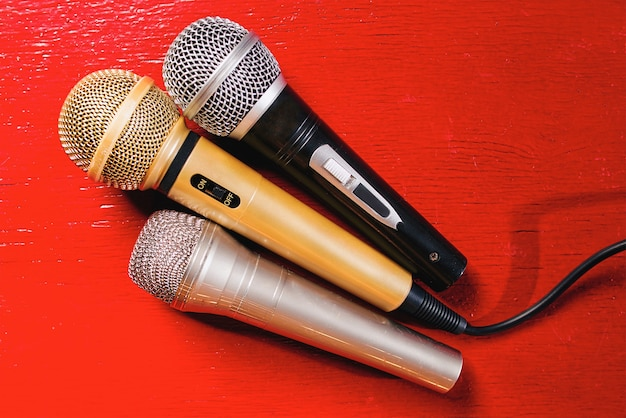 Gold silver and bronze microphones on red wooden background