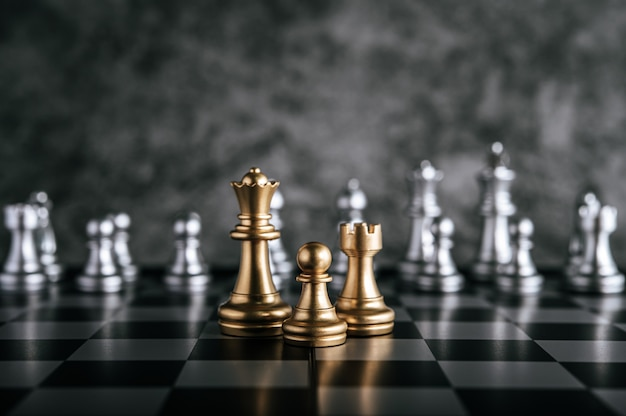 Gold and silver chess on chess board game for business metaphor leadership concept