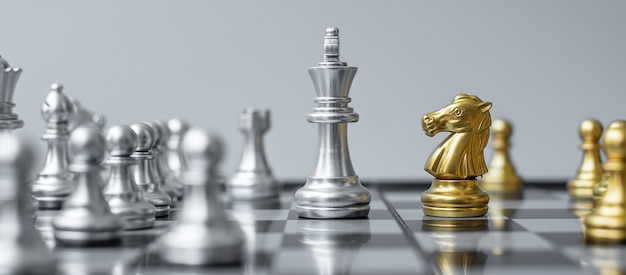 Gold and silver chess figure on chessboard against opponent or enemy.