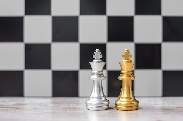 Gold and silver chess king figure on chessboard against opponent or enemy. strategy, conflict, management, business planning, tactic, politic, communication and leader concept
