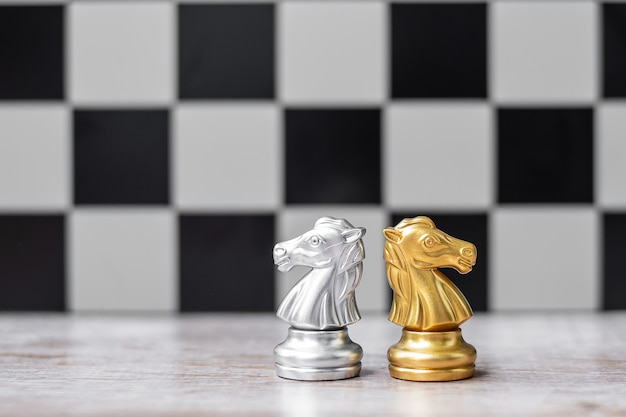 Gold and silver chess knight figure with businessman manager background.