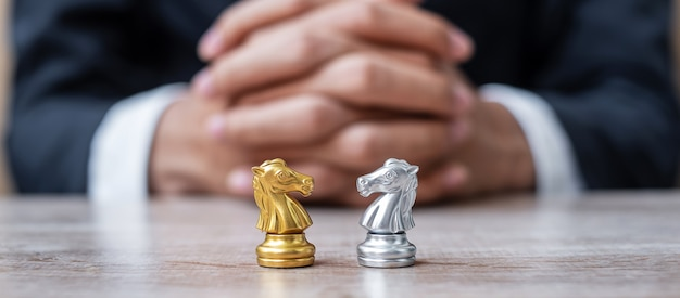 Gold and silver chess knight (horse) figure with businessman manager . strategy, conflict, management, business planning, tactic, politic, communication and leader concept