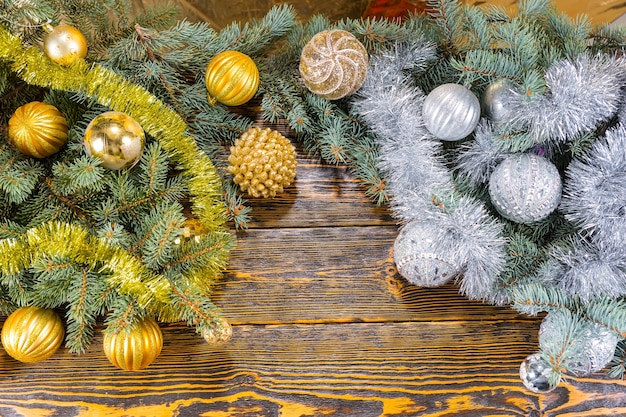Gold and silver christmas decorations on pine branches arranged as two separate colors in the corners on a rustic wooden background with copyspace between, overhead view