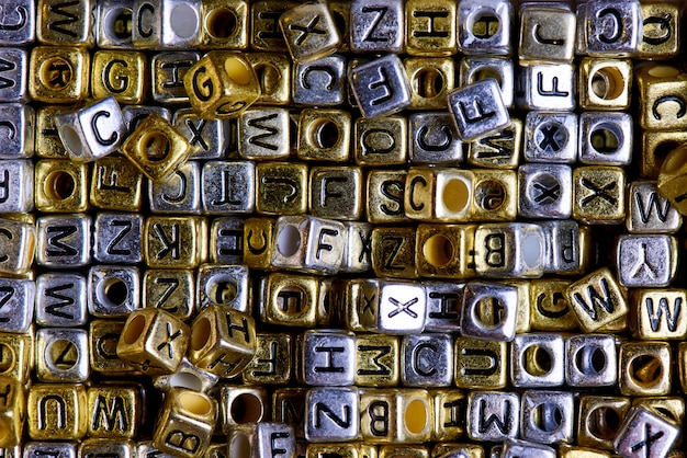 Gold and silver cubes with black english letters close-up.