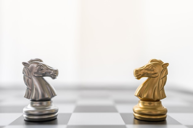 Gold and silver knight chess piece face to face on chessboard.