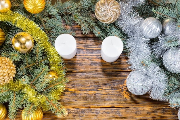 Gold and silver themed christmas still life with separate arrangements of gold and silver baubles with tinsel on pine branches separated by two white candles, overhead view with copyspace