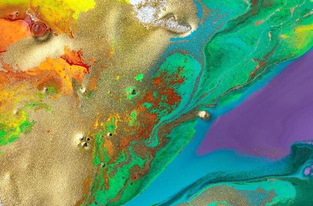 Золотые пятна на радужных пятнах абстрактного узора краски