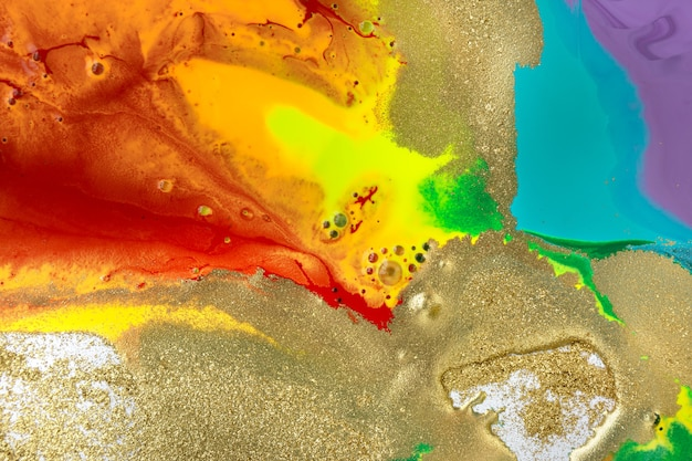 Gold spots on rainbow smudges of paint abstract pattern