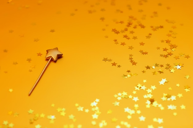 Gold star candle on a gold background with stars.