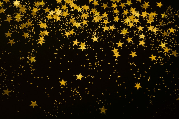 Gold star confetti and glitter on a black background  christmas new year party festive