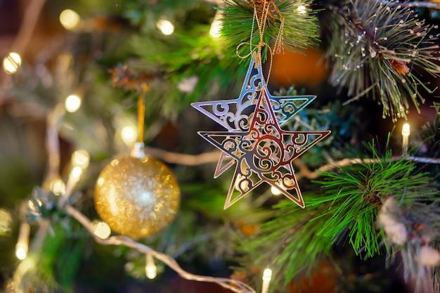 Золотая звезда висит на ветке елки. украшение елки. подготовка к празднику