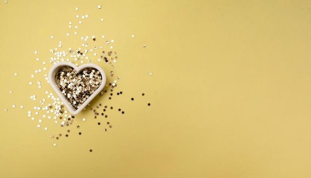 골드 스타는 발렌타인 데이 파티를위한 노란색 파스텔 유행 배경에 심장의 형태를 반짝
