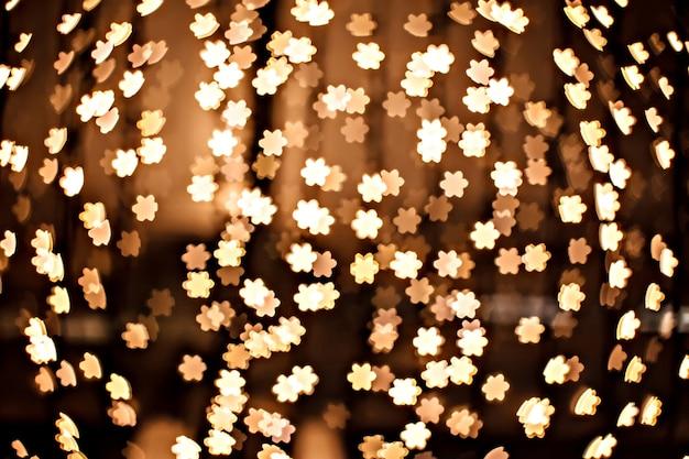 焦点がぼけた黄色の輝きとしての金の星