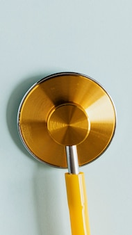 Gold stethoscope isolated on green background