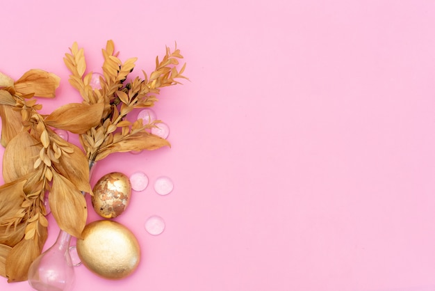 Gold stones and dried flowers on a pink background with copyspace