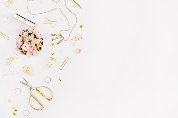 Gold style feminine accessories. golden tinsel, scissors, pen, rings, necklace, bracelet on white background. flat lay, top view.