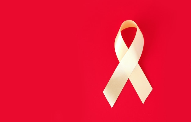 Gold symbolic ribbon on a red surface