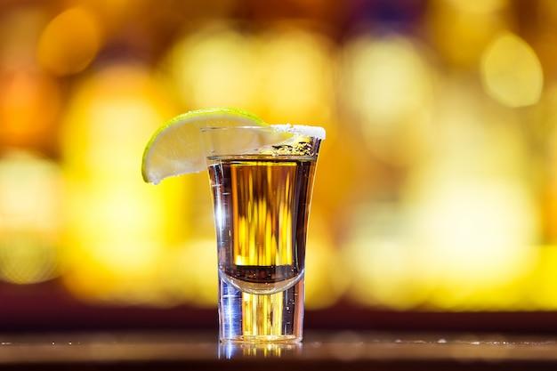 明るいライトのガラスの金のテキーラ。伝統的なメキシコの飲み物。