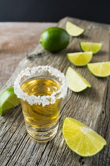 Gold tequila shot with lime slices on rustic wooden table