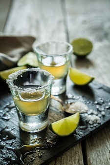 Gold tequila shots on rustic wood
