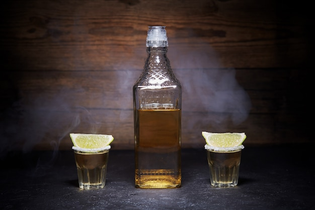 Gold tequila shots with lime fruits on wooden. bottle of tequila. smoke.
