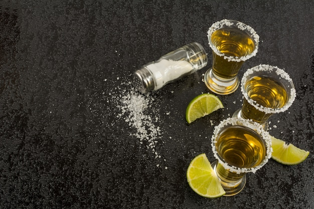 Gold tequila with lime on black background, top view
