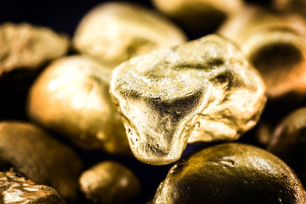 Gold texture, many gold nugget, stone of value. crude gold drawn on black surface. concept of wealth or luxury.