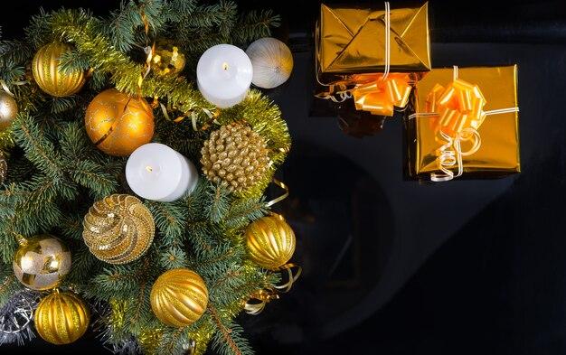 ゴールドをテーマにしたクリスマスの背景、2つの装飾的なギフト、キャンドル、つまらないものと松の枝の配置、コピースペース付きの黒の俯瞰図