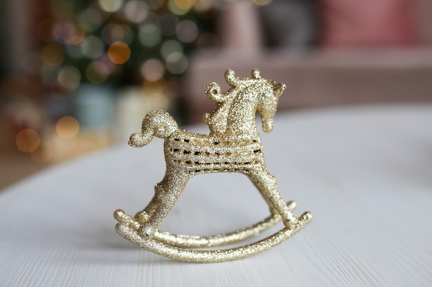 木のボケと花輪を背景にテーブルの上に立っている金のおもちゃの装飾馬