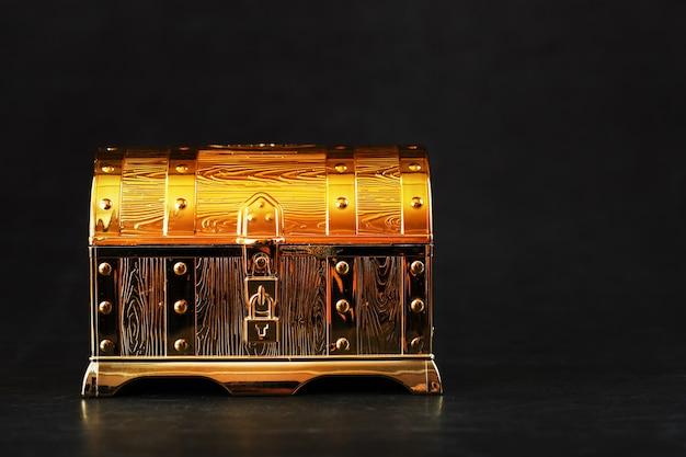 Золотой сундук с сокровищами на черной поверхности
