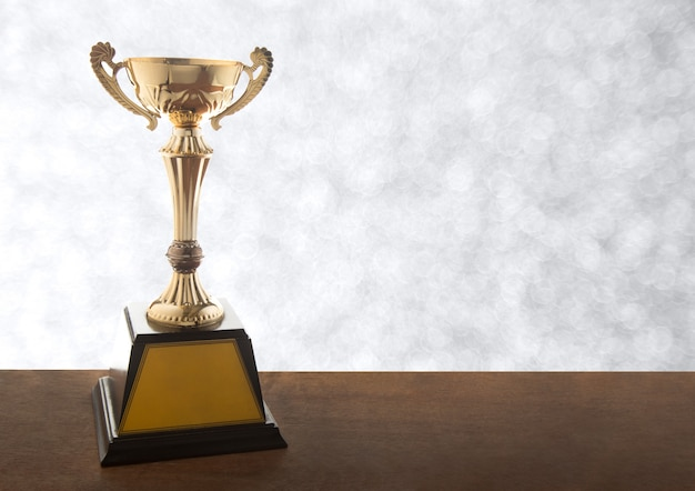 Gold trophy on wooden table on bokeh background. winning awards with copy space.
