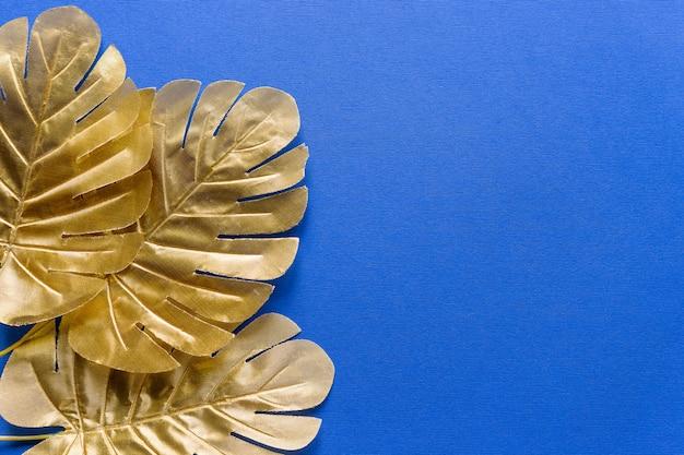 ゴールドの熱帯のヤシは、青の背景にモンステラを残します。夏休み、旅行のコンセプトです。招待カードテンプレート。