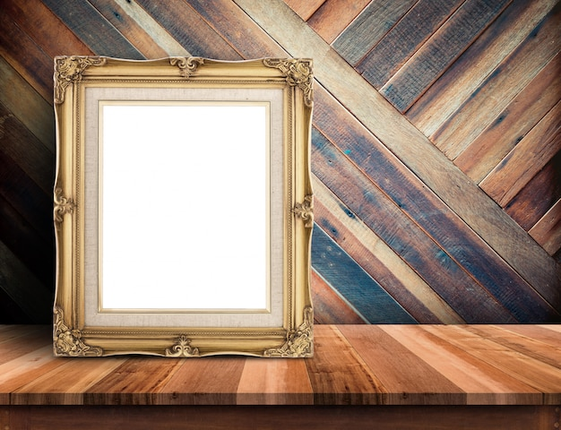 Gold victorian picture frame on plank wooden table top at tropical diagonal wood wall
