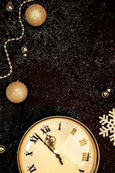 Gold vintage clock decorated with christmas balls on a black background in sparkles
