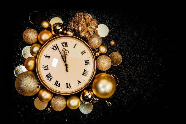 きらめきの黒い背景にクリスマスボールで飾られたゴールドのヴィンテージ時計。十二時、正月がやってきます。スペースをコピーします。