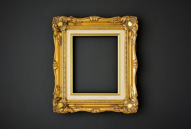 Gold vintage picture frame on black color wall background