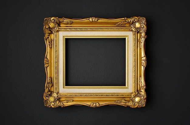Gold vintage picture frame on black color wall, copy space, funeral and mourning concept
