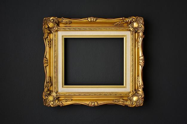 Золотая винтажная фоторамка на черном цвете стены, концепция пространства, похороны и траура