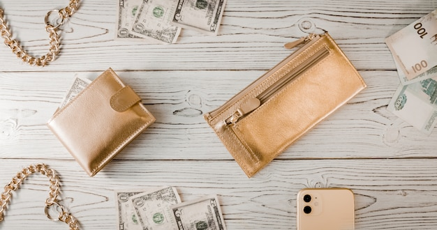 Gold wallets, a gold chain, dollars, rubles, an expensive smartphone on a wooden background